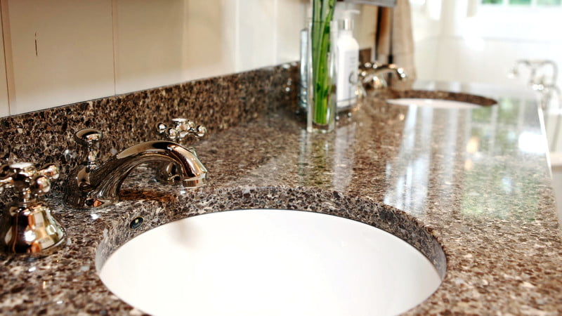 A close up of an undermount sink in a bathroom.